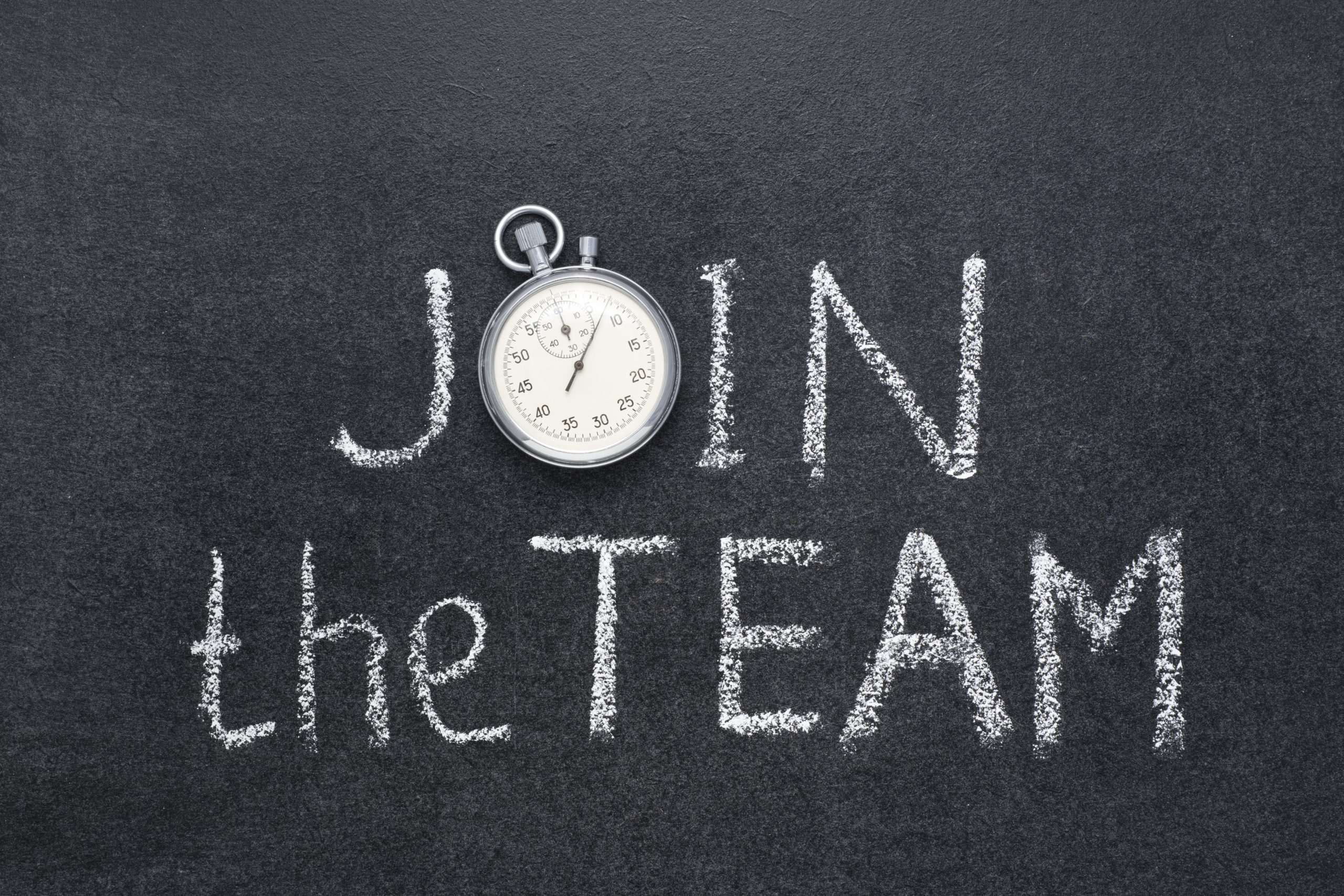 join the team phrase handwritten on chalkboard with vintage precise stopwatch used instead of O